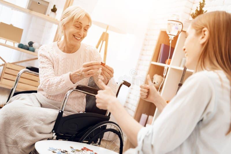 Девушка нянчит пожилую женщину дома Они кладут совместно головоломку стоковое изображение