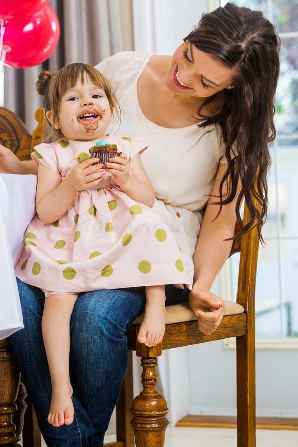 Девушка дня рождения есть пирожное пока сидящ дальше стоковые изображения