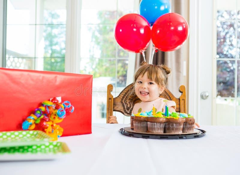 Девушка дня рождения с тортом и настоящий момент на таблице стоковое изображение rf