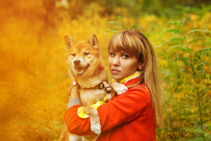 Девушка обнимает собаку Shiba Inu в парке осени стоковая фотография rf