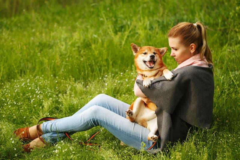 Девушка обнимает собаку Shiba Inu стоковые изображения