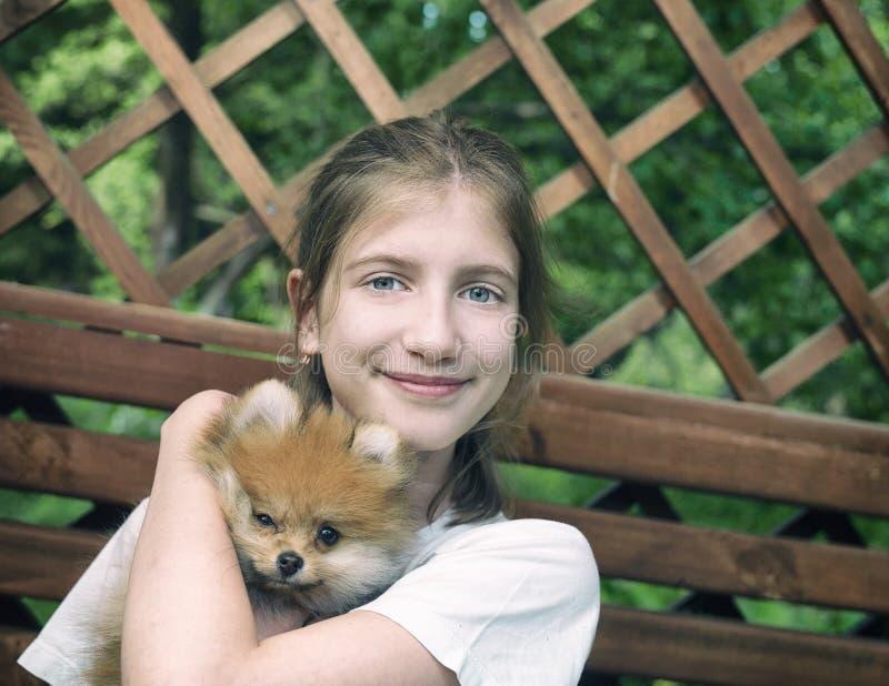 Девушка обнимая маленькую собаку стоковое изображение rf