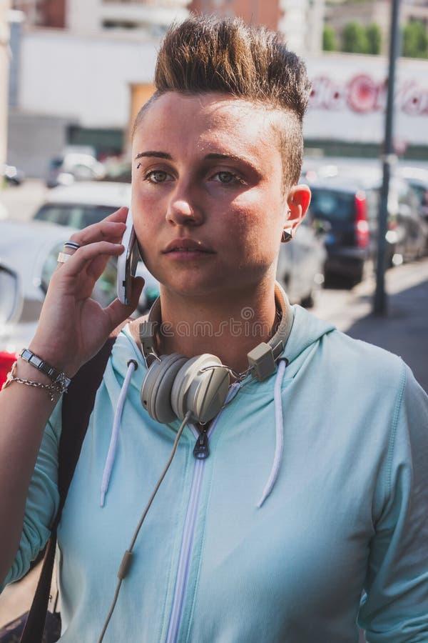 Девушка довольно коротких волос говоря на телефоне стоковое изображение