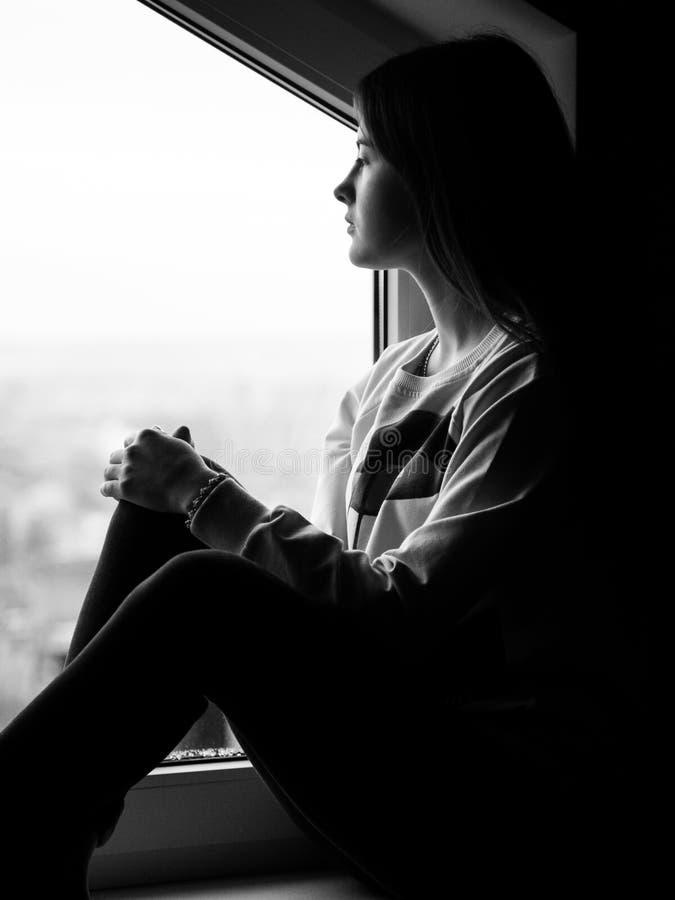 Девушка около окна Взгляд в расстоянии и mysterio стоковые фото