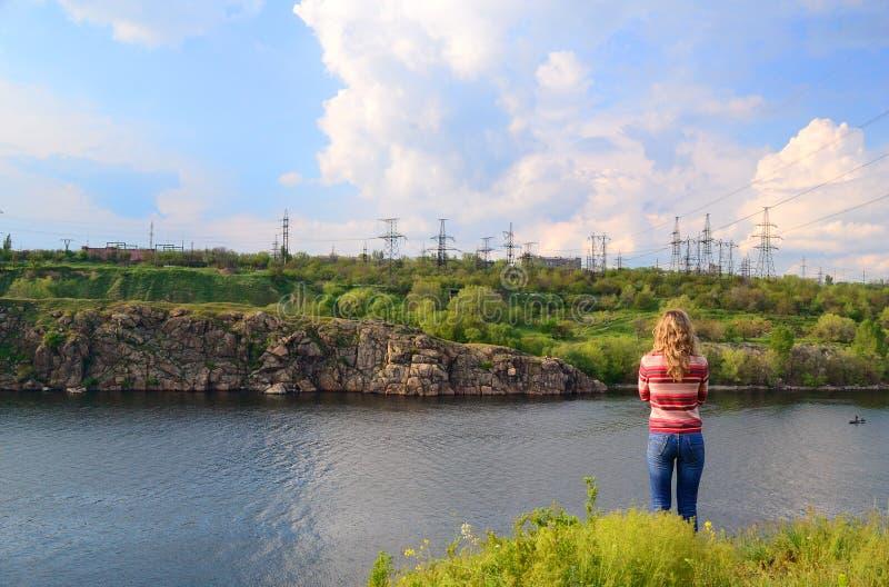 Девушка около реки смотрит afar стоковая фотография rf