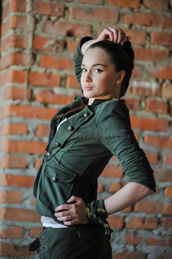 Девушка около кирпичной стены в стиле войск стоковая фотография rf
