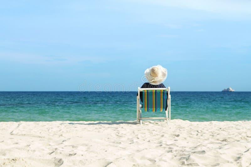 Девушка ослабляя на пляже стула стоковые изображения