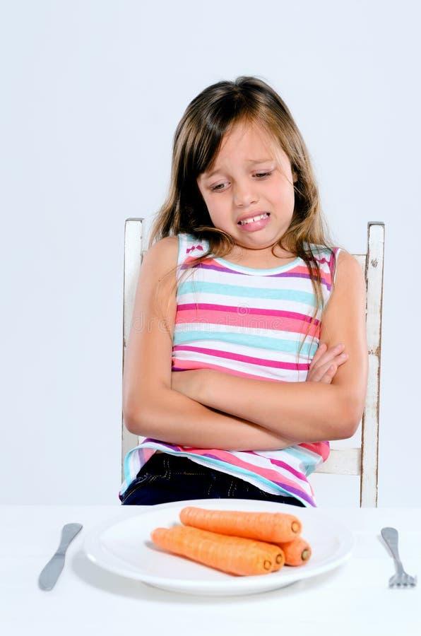 Девушка отвергает овощи с хмурым взглядом стоковые фото