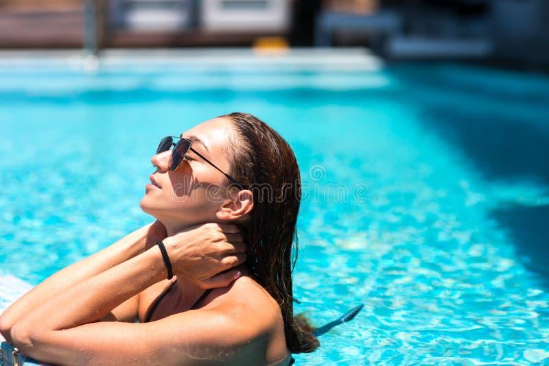 Девушка отдыхает в бассейне на пляже океана красивое брюнет с диаграммой которая путешествует стоковое фото rf