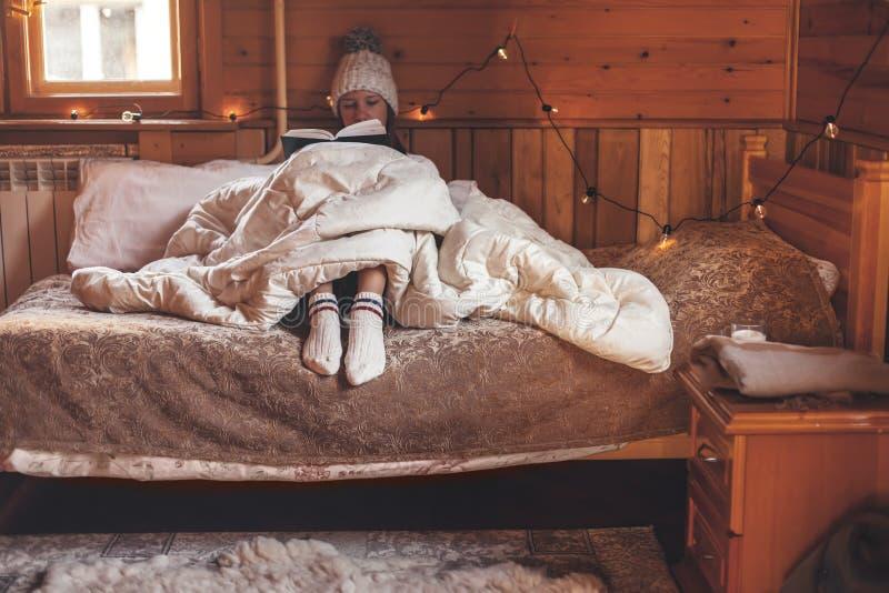 Девушка отдыхает и читает книгу в уютной хижине-логе зимой стоковая фотография rf