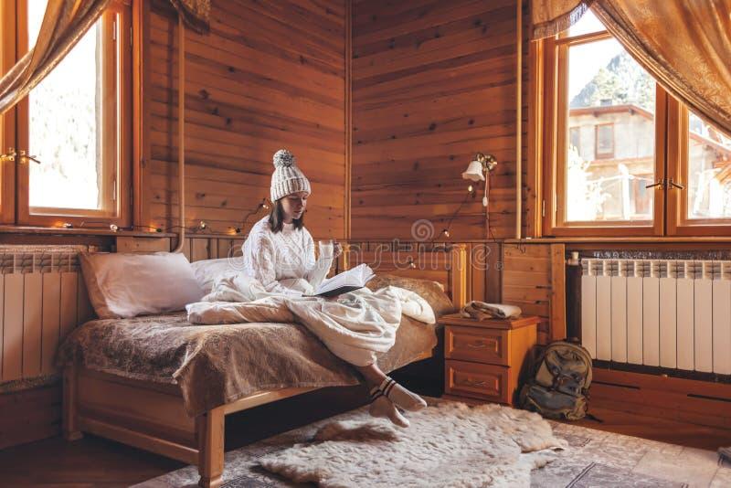 Девушка отдыхает и читает книгу в уютной хижине-логе зимой стоковые фотографии rf