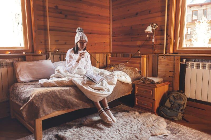 Девушка отдыхает и читает книгу в уютной хижине-логе зимой стоковое фото rf