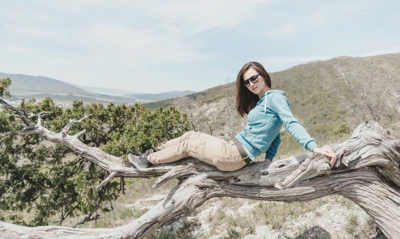 Девушка отдыхая на дереве можжевельника стоковые фото