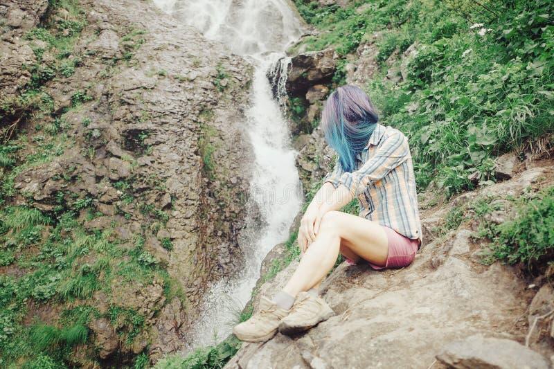 Девушка отдыхая около водопада стоковое фото