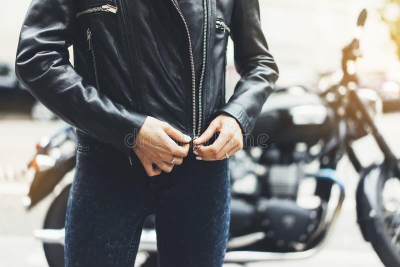 Девушка открепляет черную кожаную куртку на мотоцикле предпосылки в городе пирофакела солнца атмосферическом, крупном плане рук ж стоковые изображения rf