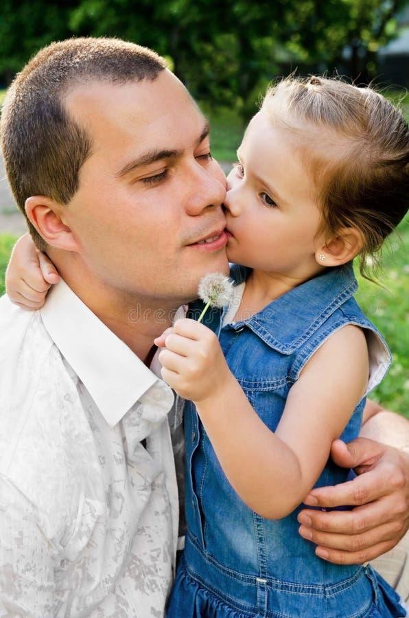 девушка отца ее целуя немногая стоковое изображение rf