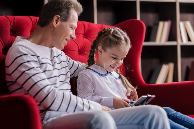 Девушка отдыхая с ее дедом и держа консоль игры стоковые фото