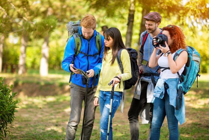 Девушка от hikers собирает фотографировать до тех пор пока другие не будут смотреть карту стоковое изображение rf