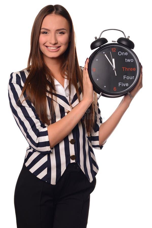 Девушка офиса показывая часы изолированные на белой предпосылке стоковое изображение rf