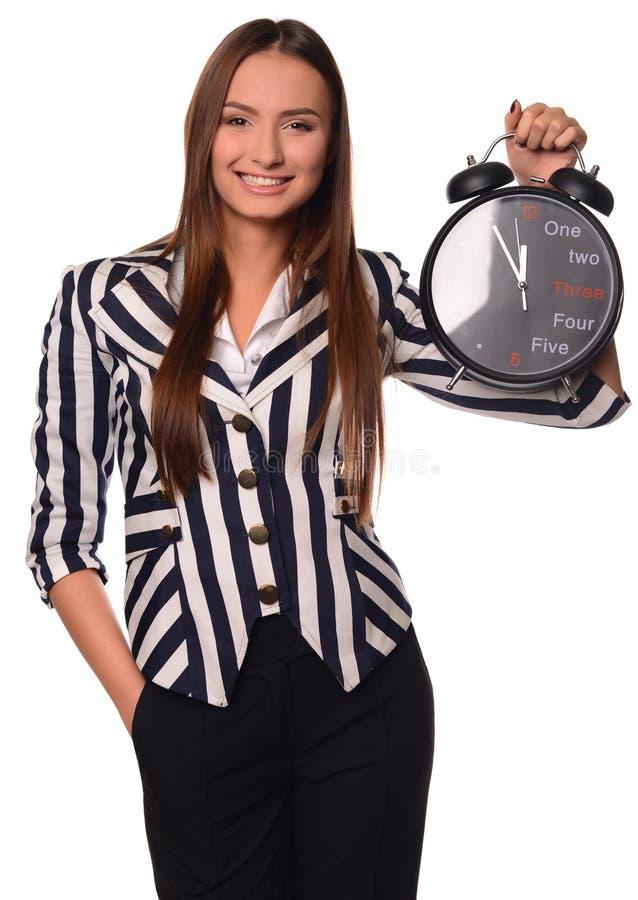 Девушка офиса показывая часы изолированные на белой предпосылке стоковые изображения