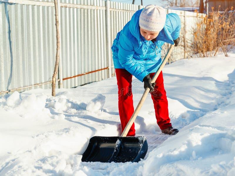 Девушка очищает лопаткоулавливатель снега на месте около его дома sunlight стоковые изображения