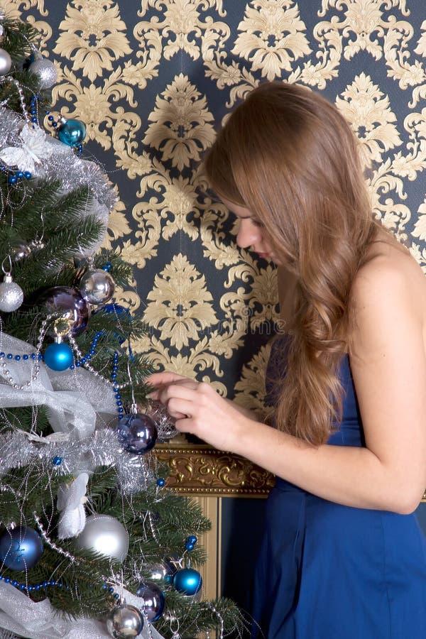 Девушка одевает рождественскую елку стоковые фотографии rf