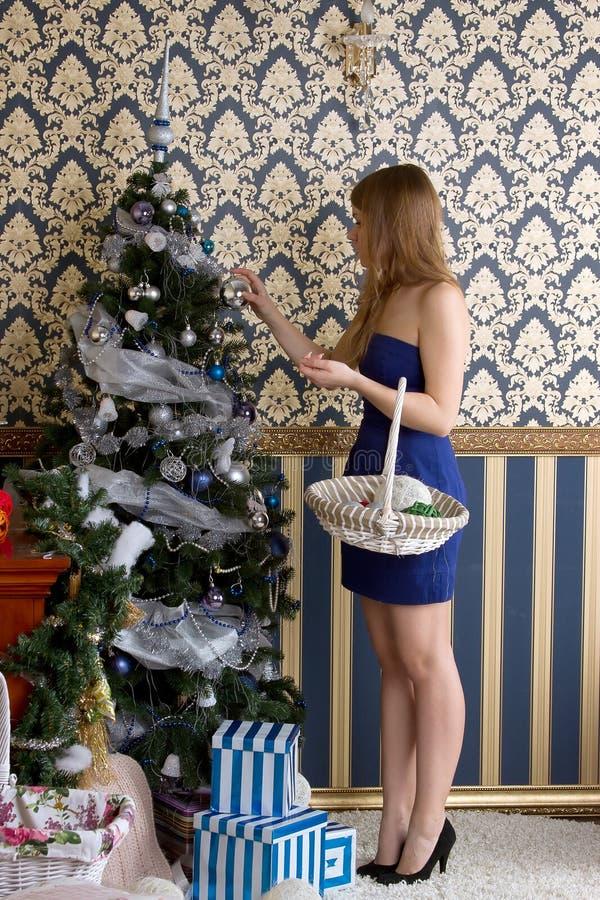 Девушка одевает рождественскую елку стоковое фото