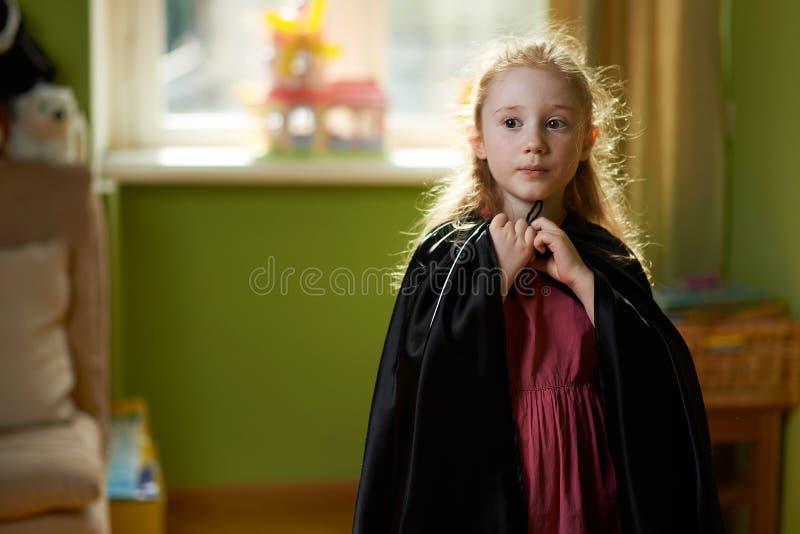 Девушка одевает черную накидку стоковое фото rf