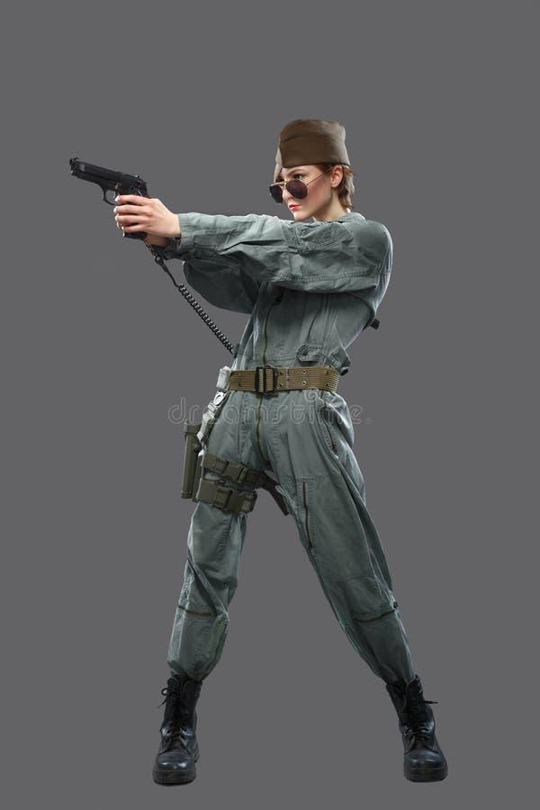 Девушка одетая как пилот вертолета с оружием в его руке стоковое фото