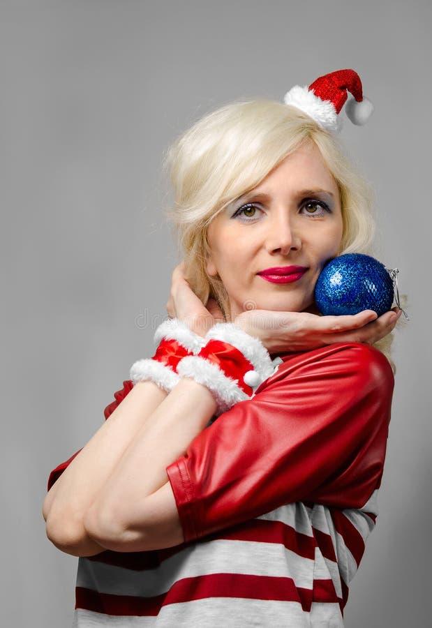 Девушка одетая как Санта Клаус с шариком рождества стоковая фотография