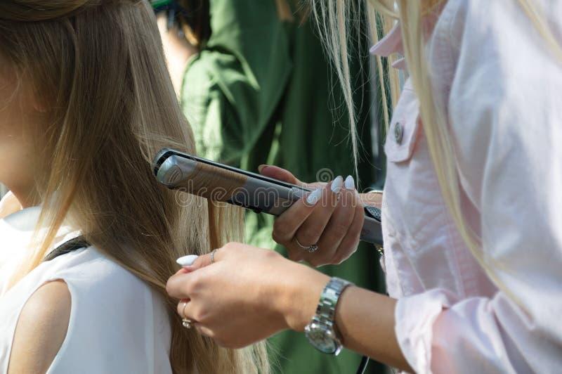 Девушка парикмахера обматывает ее волосы с утюгом Конец-вверх стоковое изображение
