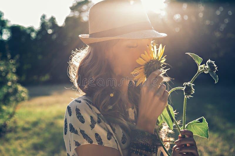 Девушка пахнет солнцецветом стоковые изображения rf