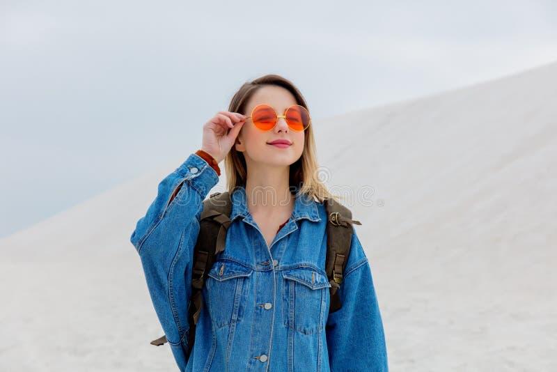 Девушка перемещения с рюкзаком в солнечные очки на пляже песка стоковое изображение