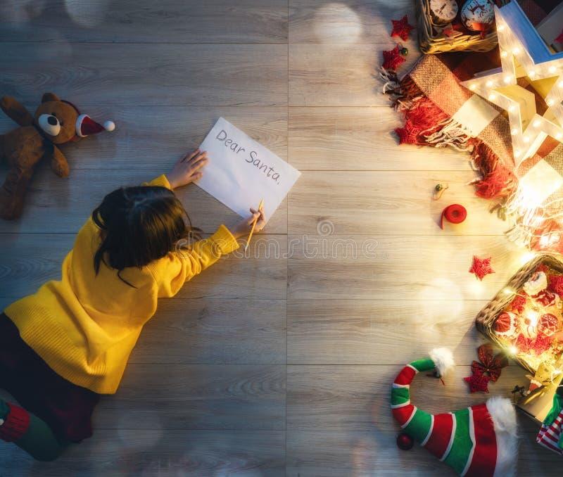 Девушка писать письмо к Санта Клаусу стоковые фото