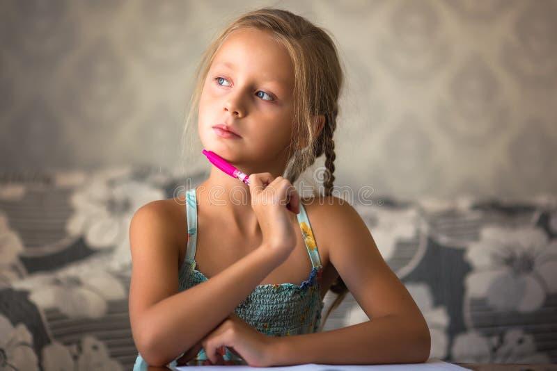 Девушка пишет в тетради Уроки решения Девушка думает над уроками стоковые изображения rf