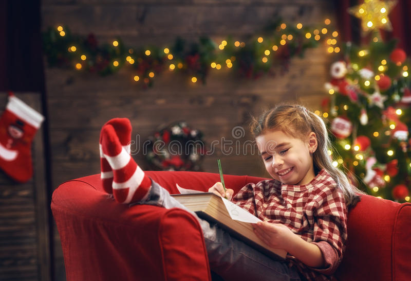 Девушка пишет письмо к Санте стоковое фото rf