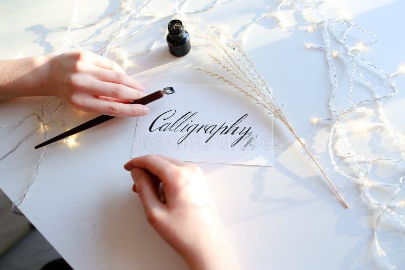 Девушка пишет фонтану ручки каллиграфические письма, сидя на таблице стоковые фотографии rf