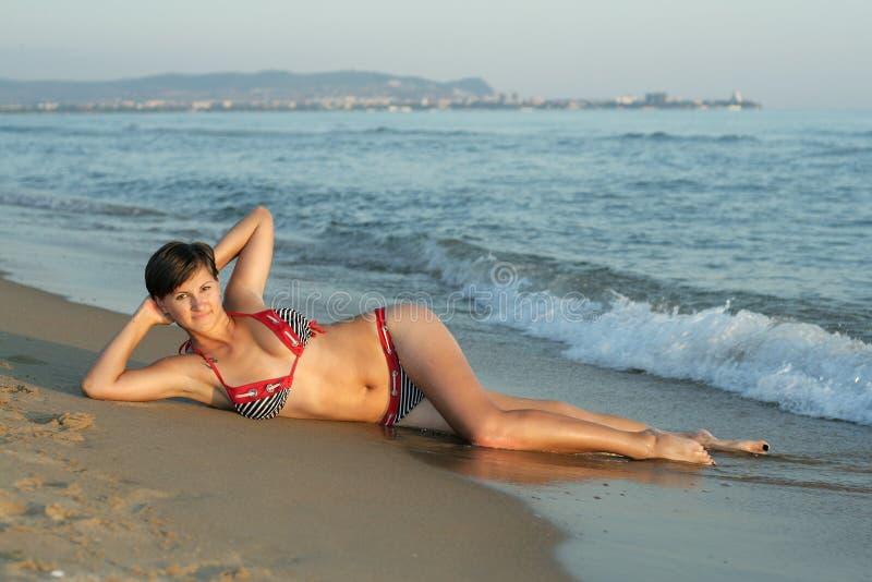 девушка пляжа кладет детенышей стоковое изображение rf