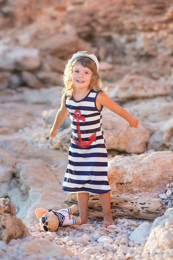 Девушка пляжа милая представляя на скалистом пляже босоногом со стеклами платья и солнца матроса вьющиеся волосы нося стоковые фотографии rf