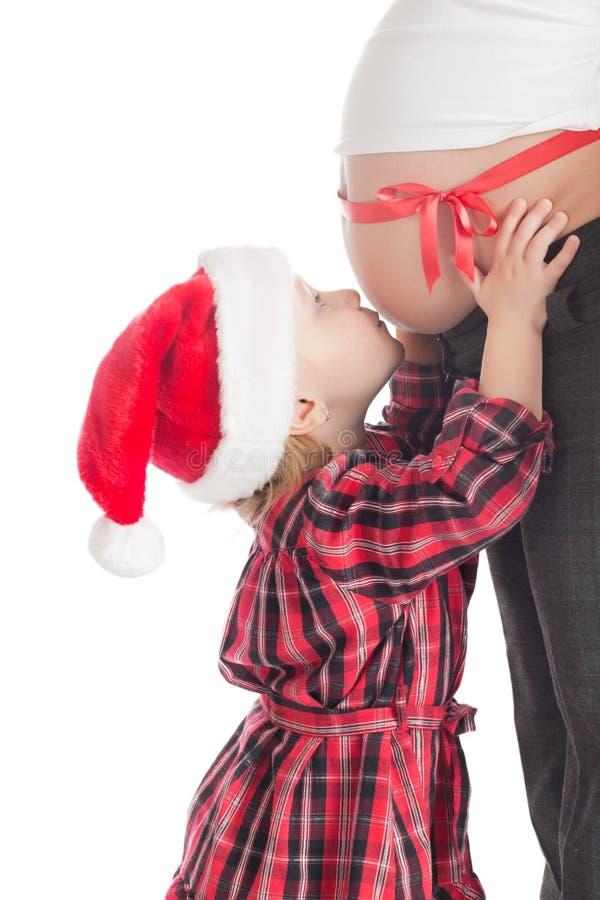 девушка подарка рождества целуя мать супоросую стоковое изображение