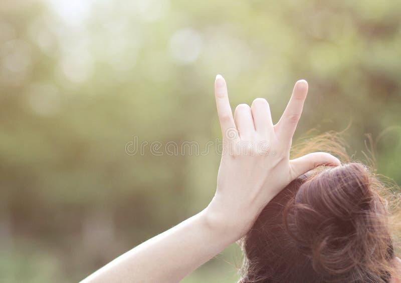 """Девушка поднимает ее руку положенную на ее головное делая  you†влюбленности """"I знака 3 пальца стоковые фото"""