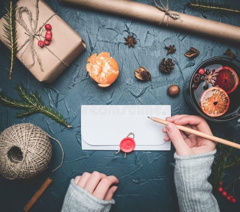Девушка подписывает конверт с поздравлениями для Нового Года или рождества, следующих лож подарка, tangerines, материалов упаковк стоковые изображения rf