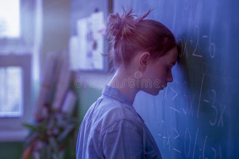 Девушка подростка в классе математики сокрушанном формулой математики Давление, концепция образования стоковое изображение