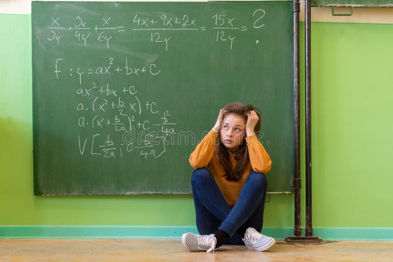 Девушка подростка в классе математики сокрушанном формулой математики Давление, концепция образования стоковое фото