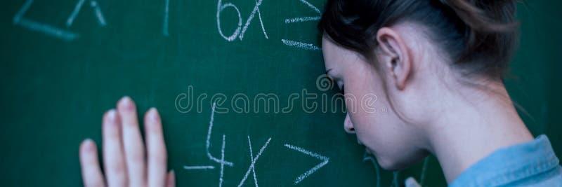 Девушка подростка в классе математики сокрушанном формулой математики Давление, образование, концепция успеха стоковая фотография rf