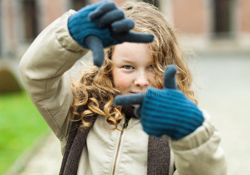 Девушка подростка делая рамку с ее перстами стоковая фотография rf