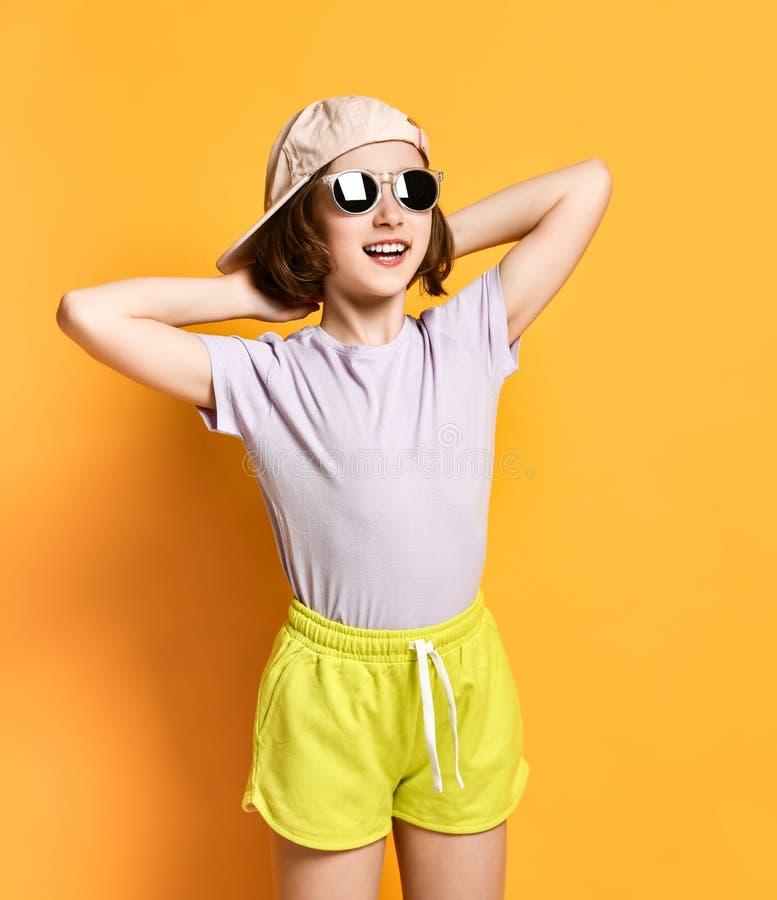 Девушка подростка моды милая крутая в солнечных очках и светлых крышке, шляпе и шортах на желтой предпосылке стоковое фото rf