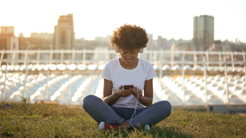 Девушка подростка сидя в красивом месте и слушая к музыке, приложению  стоковые фотографии rf