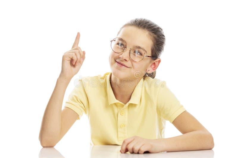 Девушка подростка со стеклами сидя на таблице, держа его указательный палец вверх o стоковое изображение rf