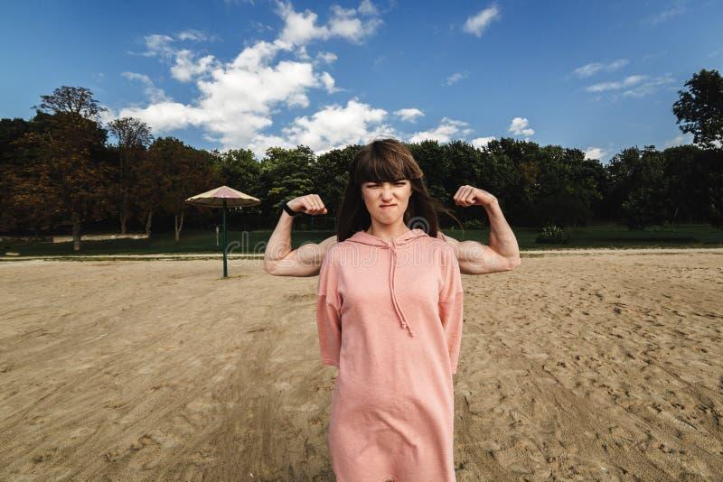 Девушка показывает ее мышцы молодые пары Худенькая девушка с сильными руками Парень за девушкой показывает бицепс стоковое фото rf